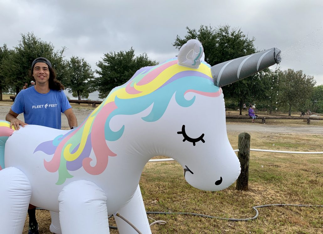 Fleet Feet Austin's Ari Perez hangs out with Brad, the water-spraying unicorn, at the 17th annual Jack's Generic Triathlon.