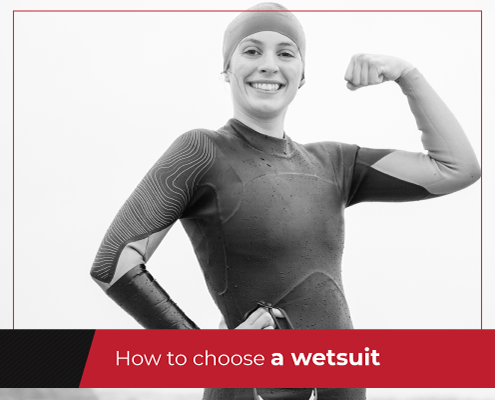 Female triathlete flexes her left arm posing in a wetsuit before a swim. Text on design reads How to Choose a Wetsuit. Learn more at https://jacksgenerictri.com/2020/10/choosing-a-wetsuit/