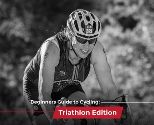 Female cyclist rides during Jack's Generic Triathlon. Text on design reads Beginner's Guide to Cycling: Triathlon Edition. Learn more at https://jacksgenerictri.com/2021/02/beginners-guide-to-cycling/